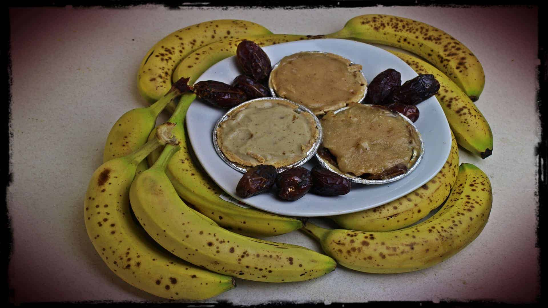 A number of ripe bananas are seen surround I white plate. Upon the plate, in aluminium tins are three delicious looking banana and date pies. The plate is also decorated with a few full dates.