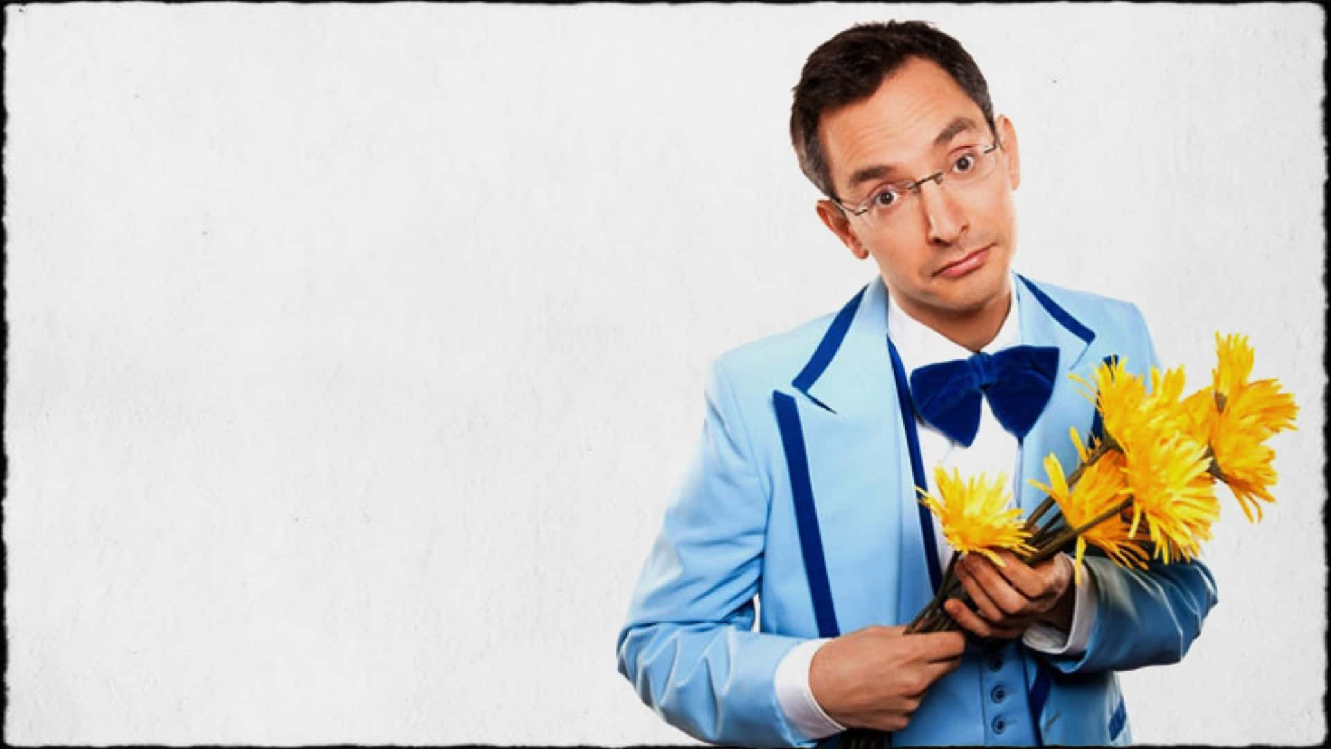 """Myq Kaplan of """"America's got talent"""" is shown in a blue dress suit, holding a bunch of flowers."""