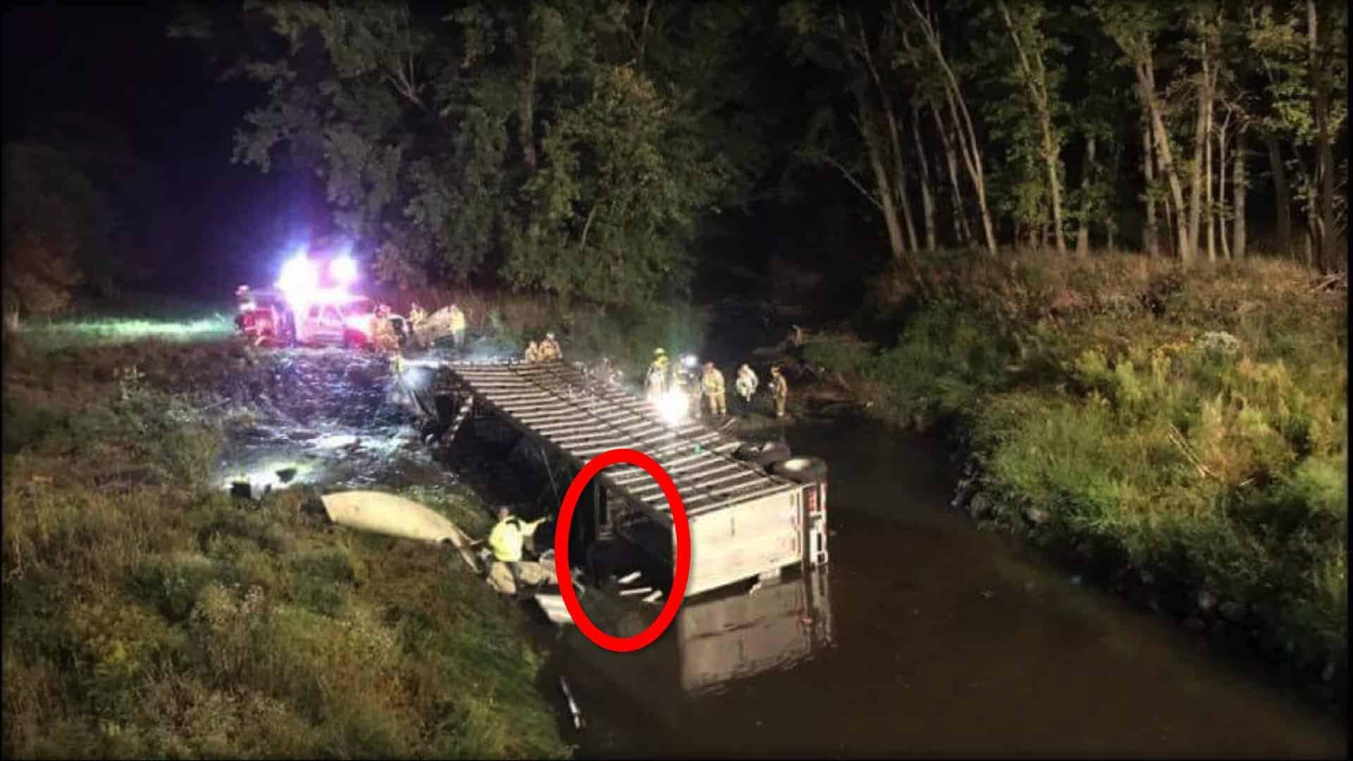 A livestock transport truck overturned on its side in a river, surrounded by rescue workers; an emergency vehicle with its lights on is in the river behind the truck, illuminating the night.