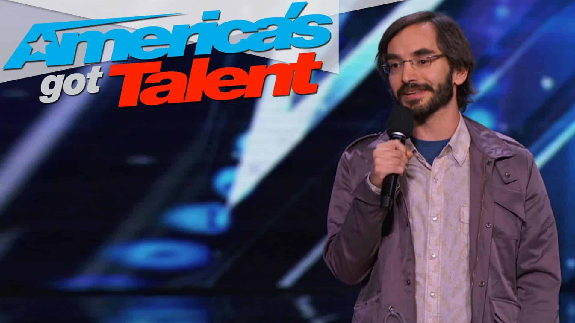 "Myq Kaplan of ""America's got talent"" is shown on stage with the ""America's got talent"" logo in the tope left hand corner."
