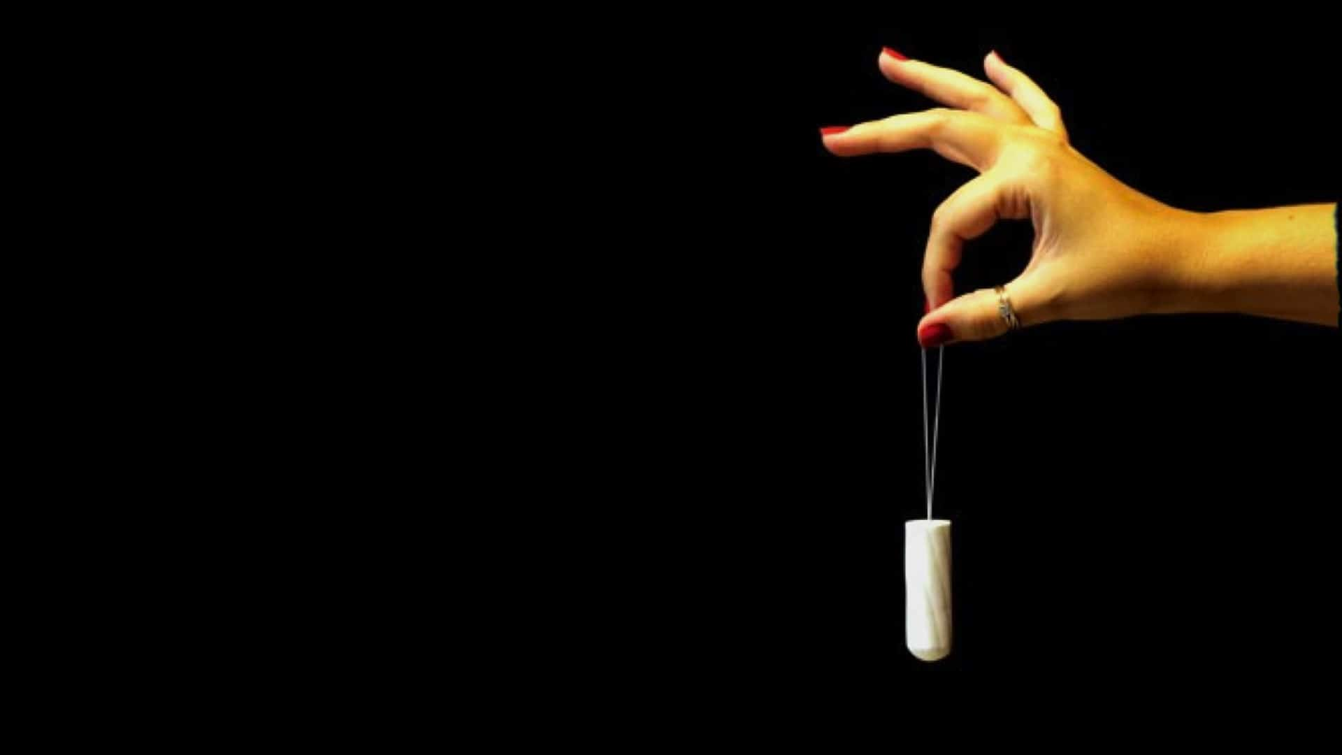 Against a dark background, from the right-hand side, a hand and forearm can be seen. The hand is holding the string of a dangling tampon between a finger and thumb.