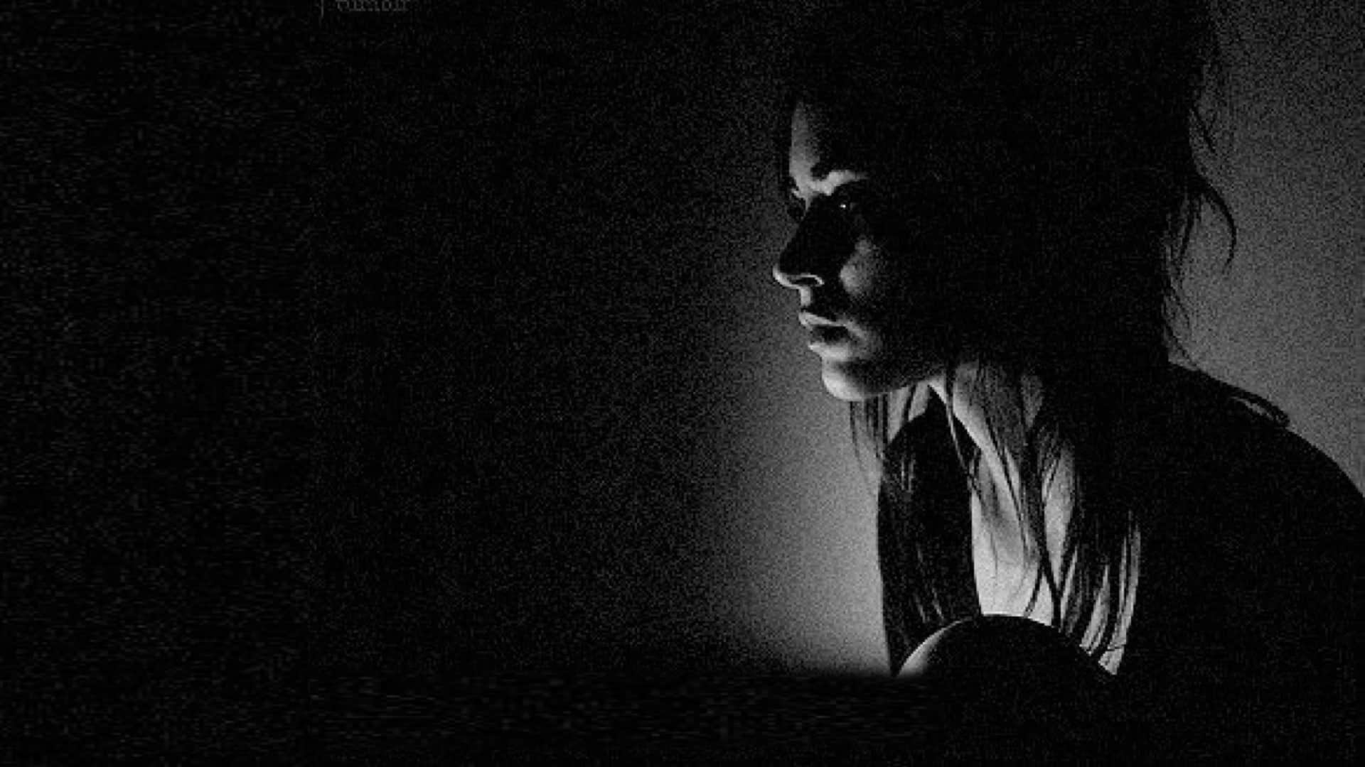 A woman suffering from depression sitting alone in the dark.