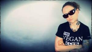 """Emily Moran Barwick of Bite Size Vegan is shown in a dark tee-shirt and shades. Her tee-shirt says """"The vegan club"""". Emily's head is tilted to one side and a look of intimidation is upon her face."""
