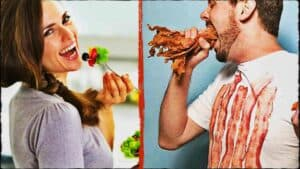The image is split in tow, vertically. On the left is a smiling person looking towards the camera. Their mouth is open and they are holding a fork filled with colorful salad. The right hand shows a second person. They are wearing a white tee-shirt with either blood or rashers of bacon down the front of it. There mouth is wide open and they are attempting to place a fist full of cooked bacon into their mouth.