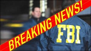 """The image shows shows two people in blue nylon jackets. One has their back to the camera and the words """"FBI"""" in yellow can be seen across the shoulders. A red and yellow banner runs diagonally from corner to corner. It states """"Breaking news."""""""