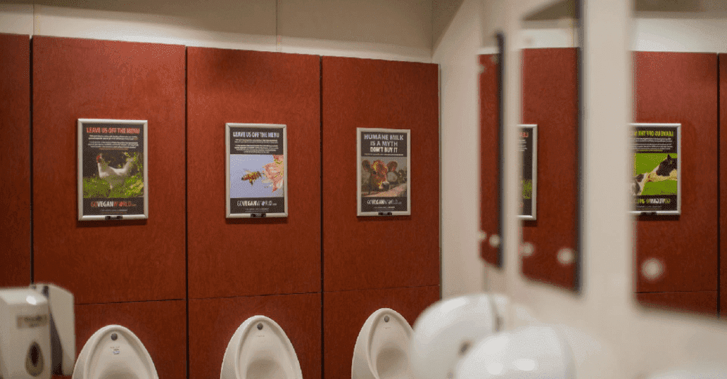 """The image is of a wall within a public bathroom.  On the wall are three framed posters.  Each is made up of text at the top, an image in the center and the GoVeganWorld.com log at the bottom. The first poster has an image of a chicken, standing on grass, with the words """"Leave us off of the menu""""  at the top with smaller writing below this.   The second poster is of a bee entering a flower.  The top text states """"Leave us off the menu."""" The final poster depicts a cow below the words: """"Human milk is a myth.  Don't buy it."""""""