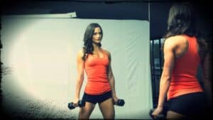 Vegan bikini athlete Samantha Shorkey is shown in the gym. She is looking at her reflection whilst she poses with two dumbbells.