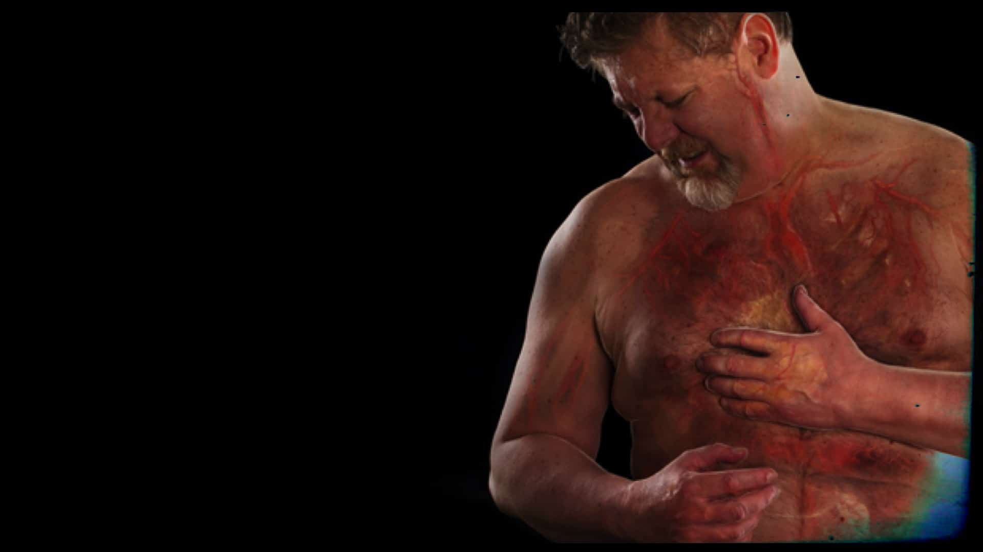 A person is shown with pain on their face. They have one hand over their heart and the other just below it as if they are suffering from chest pain. Subtly, overlaying the persons chest is an image of what is below the skin, blood vessels, bones, etc.