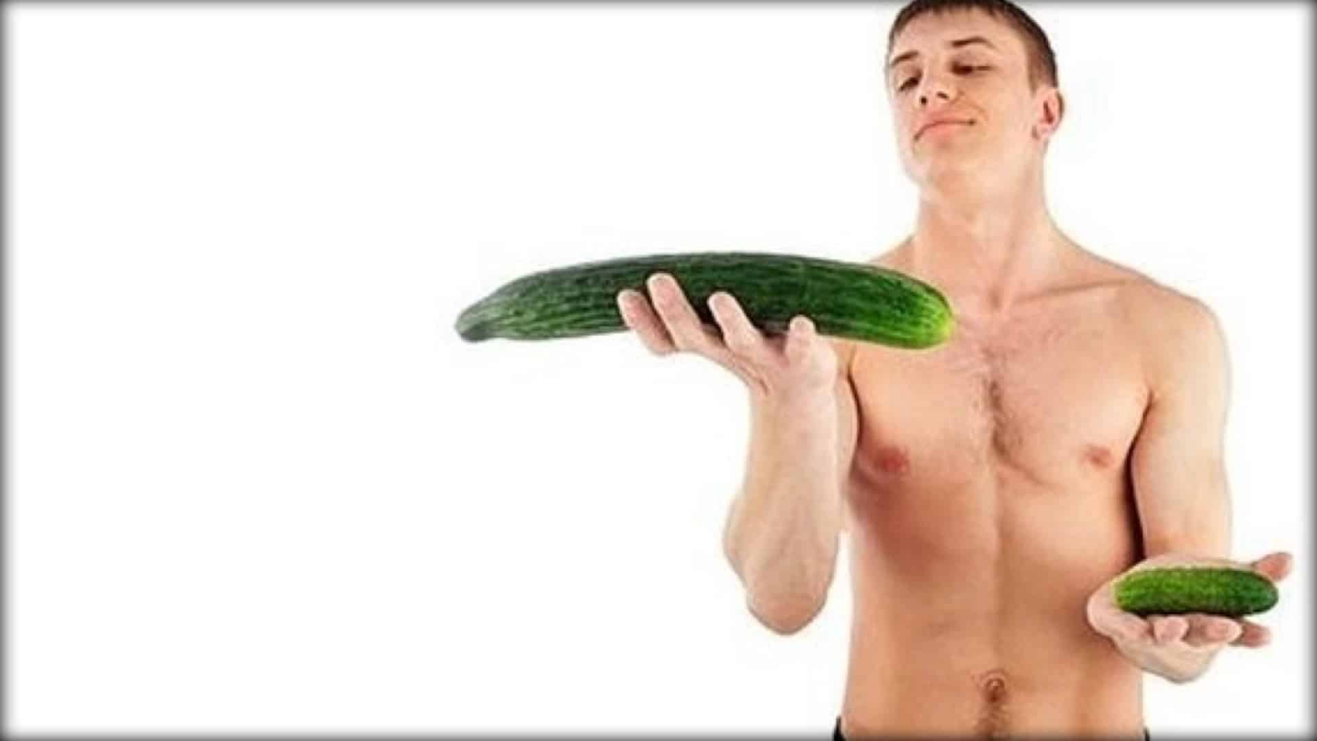 Naked man viewed from the waist up holding a small cucumber in one hand and a large cucumber in the other. The large cucumber is held higher than the small one