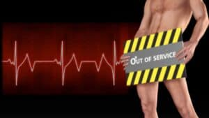 """The image has a dark background with a large ECG heart trace, in white with a red glow, running across it. On the right, in front of the trace is what appears to be a naked man. He is facing slightly to the left of the camera and is shown from his shoulders to his calves. The man is holding a sign, to cover his modesty. The sign has black and white """"warning"""" stripes top and bottom with the words """"Out of service"""" clearly written across the center."""