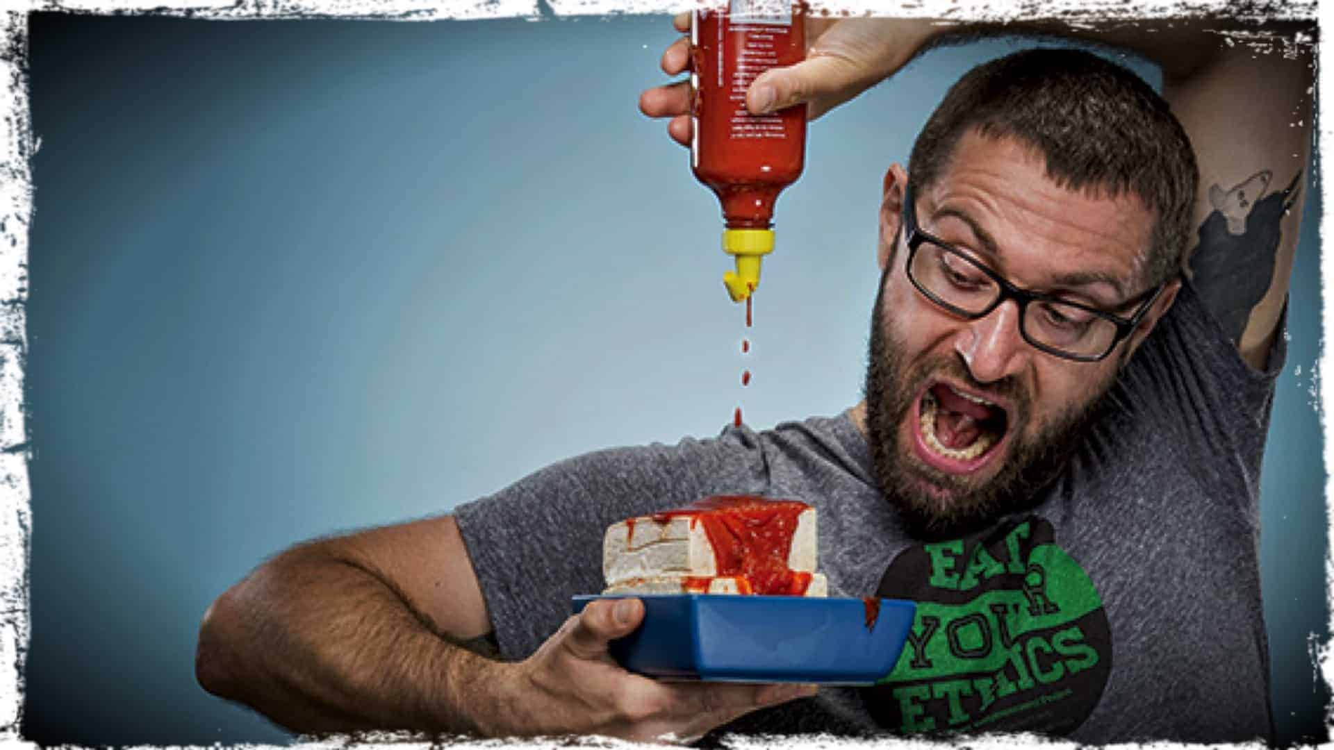 A person is shown squirting tomato sauce on to two slabs of tofu, piled one on top of the within a small food tray.