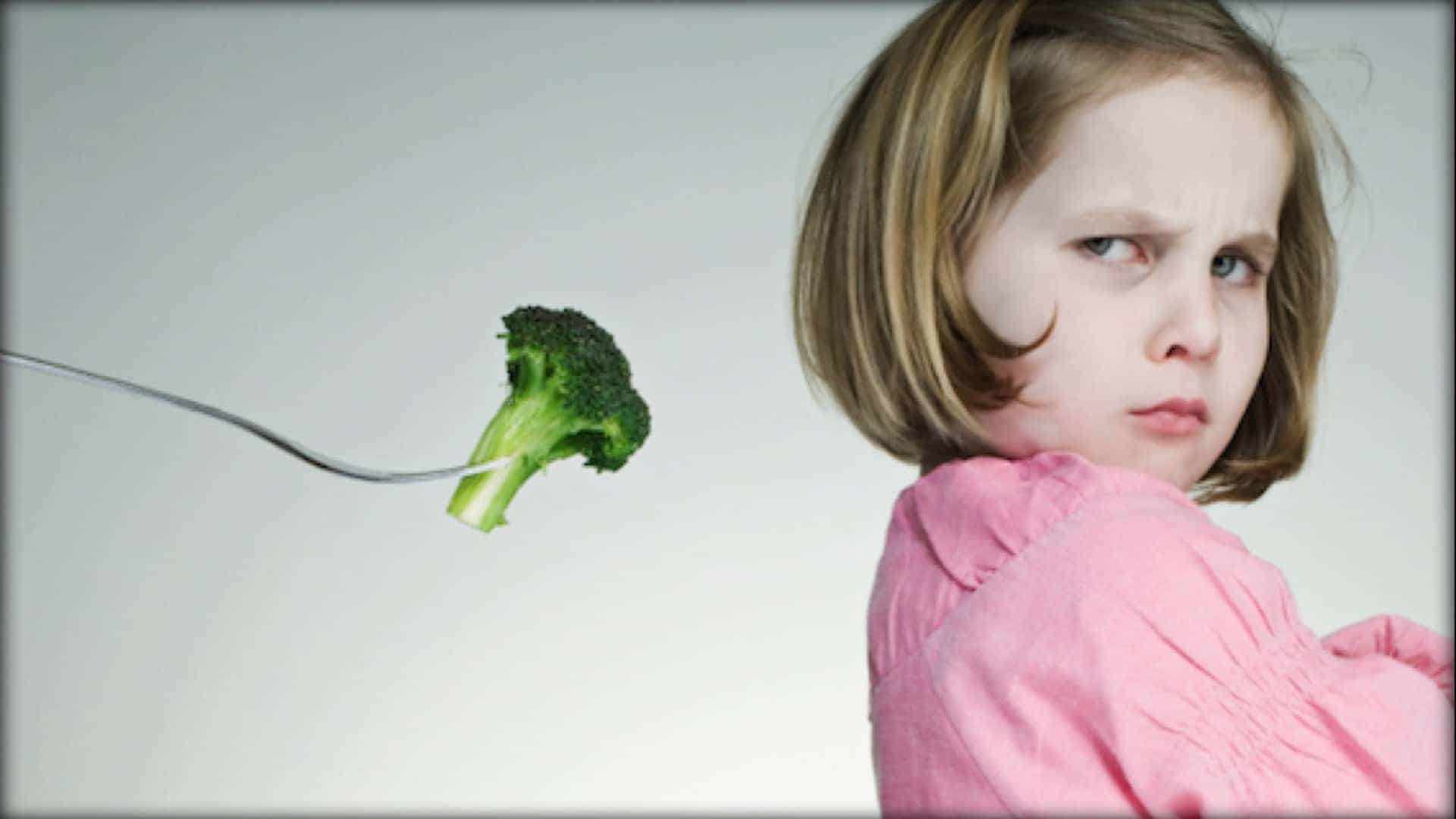 On the left is a cutlery fork. The holder is out of view. A sprig of broccoli is held within the tines of the fork. On the right is a child with their arms crossed and back towards the fork. They have their head turned and are scowling at the broccoli.