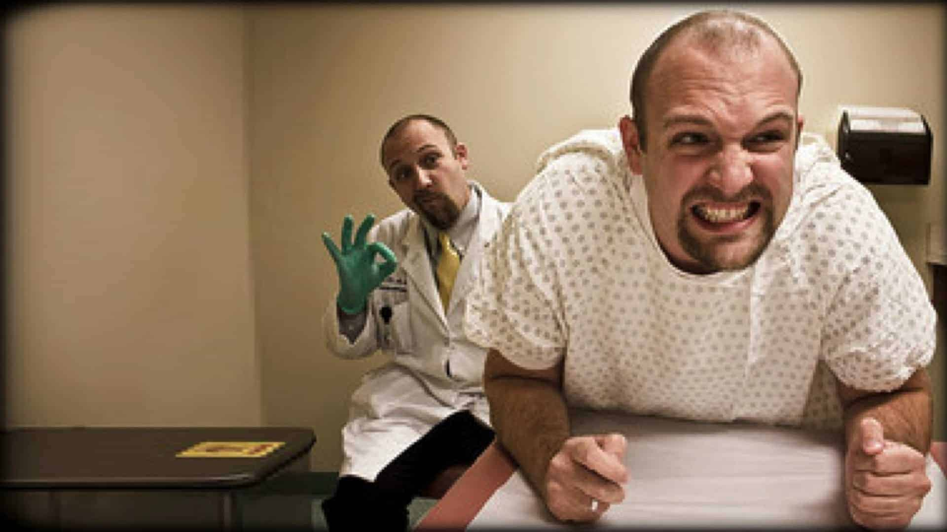 A man is shown with a grimace of pain on his face. He is wearing a surgical gown and is bent forward. A second man, dressed as a doctor in surgical gloves is behind him. His left arm is out of sight; hidden by the body of the first man.