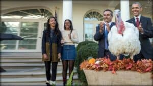 President Obama stands with his family and a member of staff in front of the White House. They applaud. In the foreground is the turkey they decided not to kill.
