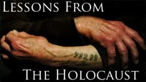 """Against a dark background, a person is shown in close up. Only the lower half of their crossed arms are visible. The sleeve of one arm is pulled up slightly revealing a tattooed identification number on their forearm. Split across the image, top and bottom, are the words """"Lessons from the holocaust"""" in large white letters."""