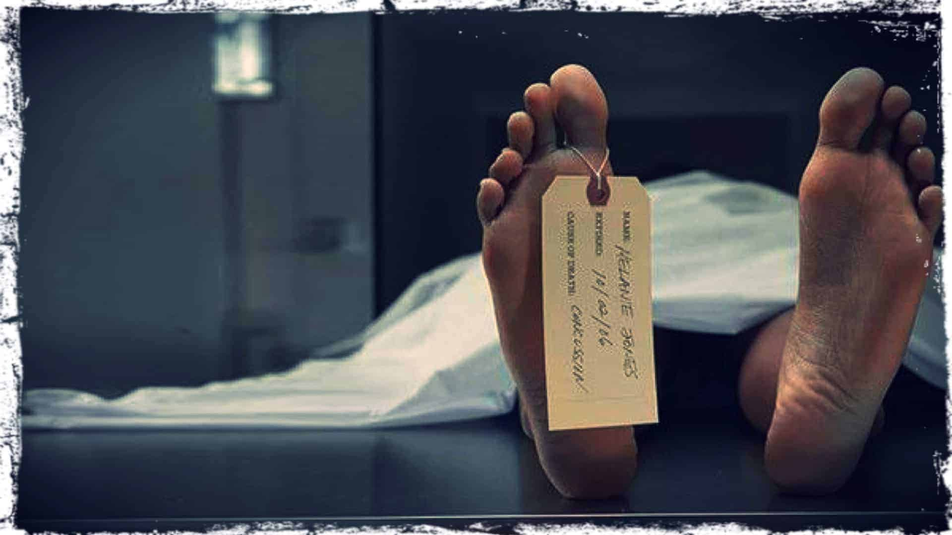 The image shows a close-up of the soles of a person's feet. They are laying on their back, covered by a sheet. A toe tag is attached to one of their feet.