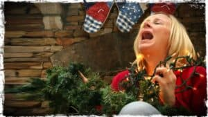 A person is shown with the branch of an artificial festive tree in one hand and festive lights in the other. Their head is back and they are letting out a scream of despair.