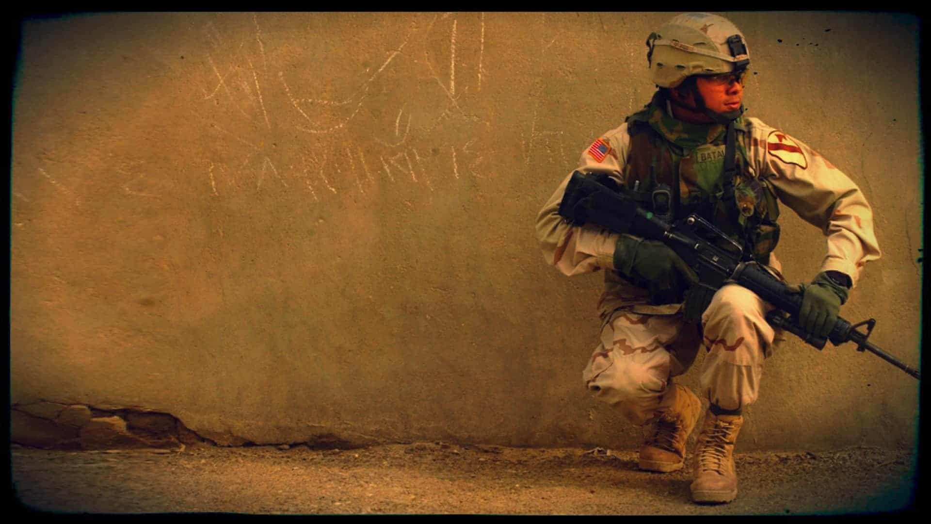 Alex Contreras, Army Sergeant and vegan, is shown in full combat gear, hunkered down against a wall. He has his weapon at the ready across his thigh.