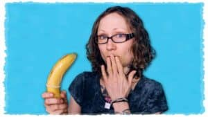 Emily Moran Barwick of Bite Size Vegan is shown holding a large banana. The banana has a condom rolled on to it. Emily is holding the fingers of her hand to her lips and showing surprize.