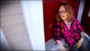 Emily Moran Barwick of Bite Size Vegan is shown in an apparent collapse, as if drunk. She is leaning up against a front door. There are marks around her mouth and chin as well as her fingers as she has been binging on cheese.