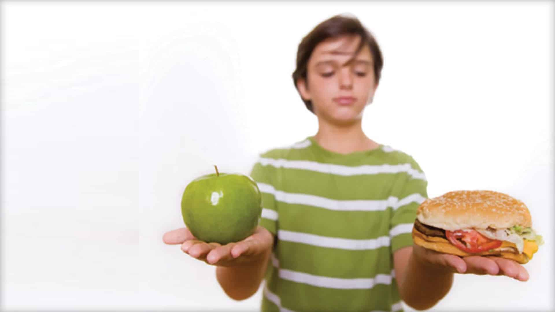 A person is shown holding an apple in one hand and a hamburger in the other. They appear to be weighing the decision of which to eat.