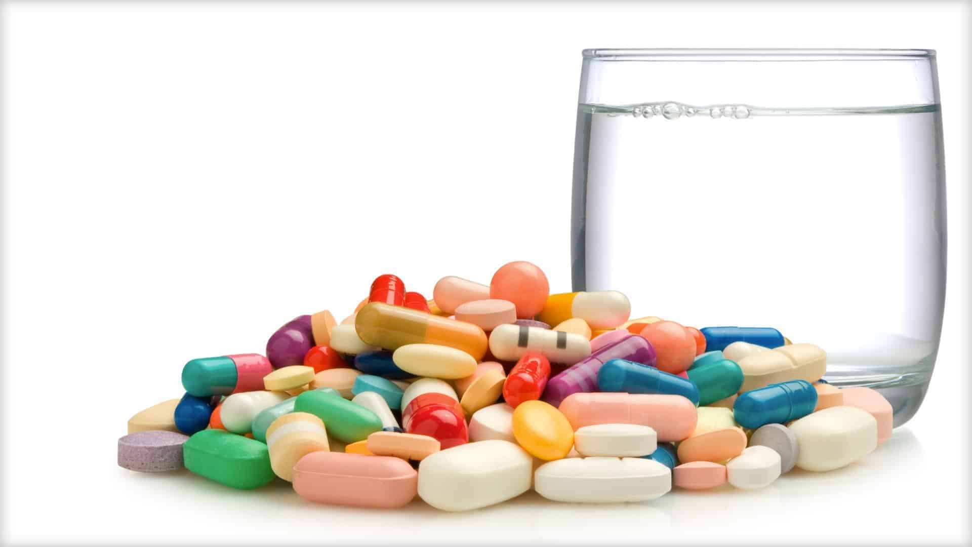 A large number of differing pills can be seen of different colors next to a glass of water.