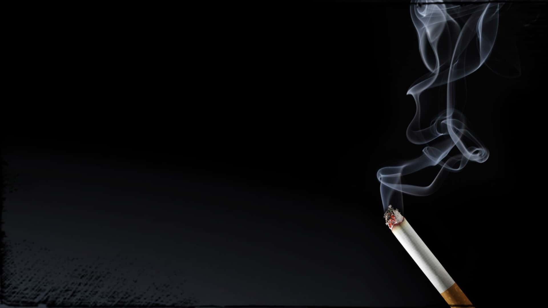 A lit cigarette with a trail of smoke rising into the air against a black background.