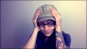 Emily Moran Barwick of Bite Size Vegan is shown looking downcast with her head in her hands.