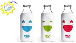"""A white and yellow star is shown in the top left-hand corner. The appearance is one rendered in crayon. Across the center of the star are the words """"For Kids"""". Across the main body of the image, three glass bottles of milk are shown. Each has a simplified, happy face upon the front. One is in blue, one green and one red. Below each face is the word Milk with the fat content in smaller print below: 2% Reduced, 1% Lowfat and Whole Milk."""