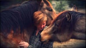 Author Ren Hurst embracing a horse who has nuzzled up to her and places his head over her shoulder, as a second horse brings her nose to Ren's.