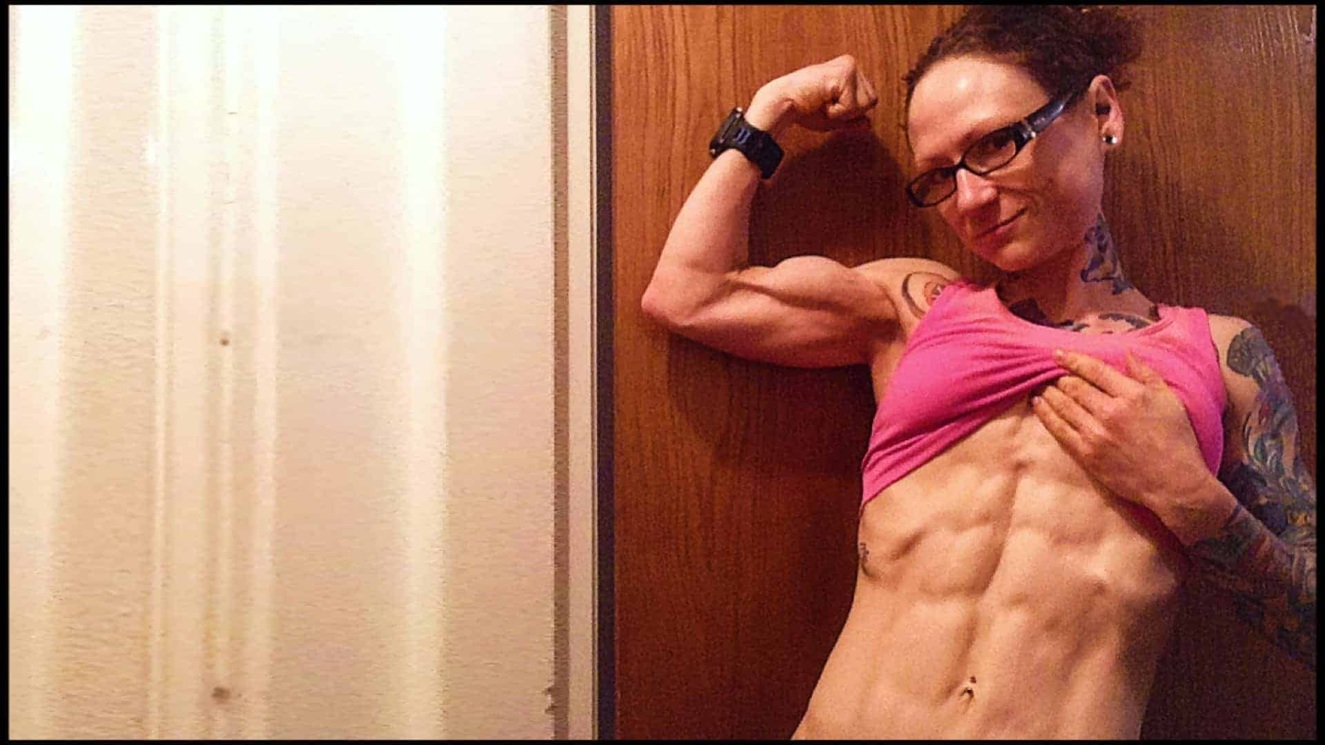 Emily Moran Barwick of Bite Size Vegan is shown from the waist up. Her right arm is curled, the muscles of her arm, clearly defined and taught. With her left arm, she is lifting up her shirt to reveal her wash-board abs and sculptured muscle definition.