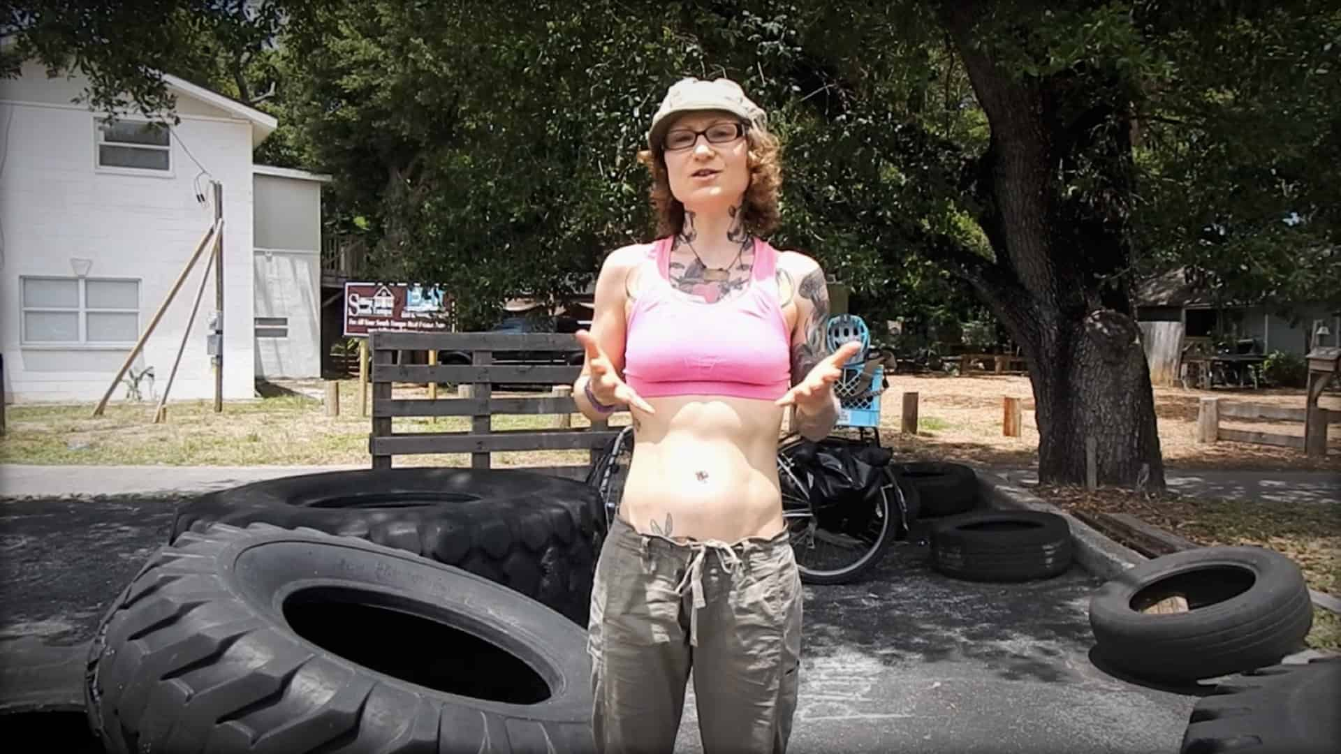 Emily Moran Barwick of Bite Size Vegan is shown in a backyard. She is wearing exercise clothing and next to a large tractor tire.