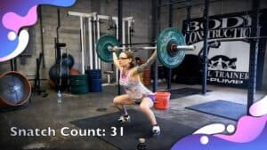 Emily Moran Barwick of Bite Size Vegan is shown lifting a weights in the snatch position.