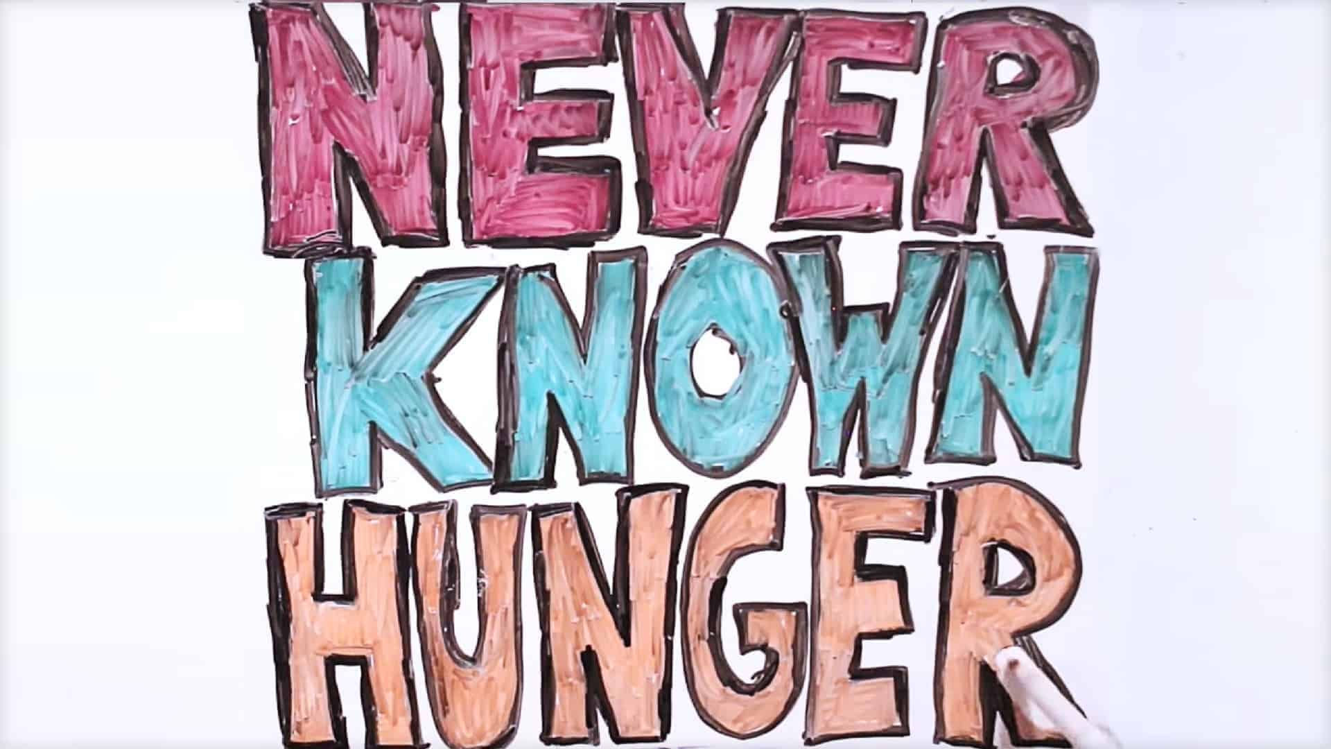 The phrase: never known hunger is written in large capital letters on a white board. Each word is a different color: red, blue and orange and the letters are outlined in black.