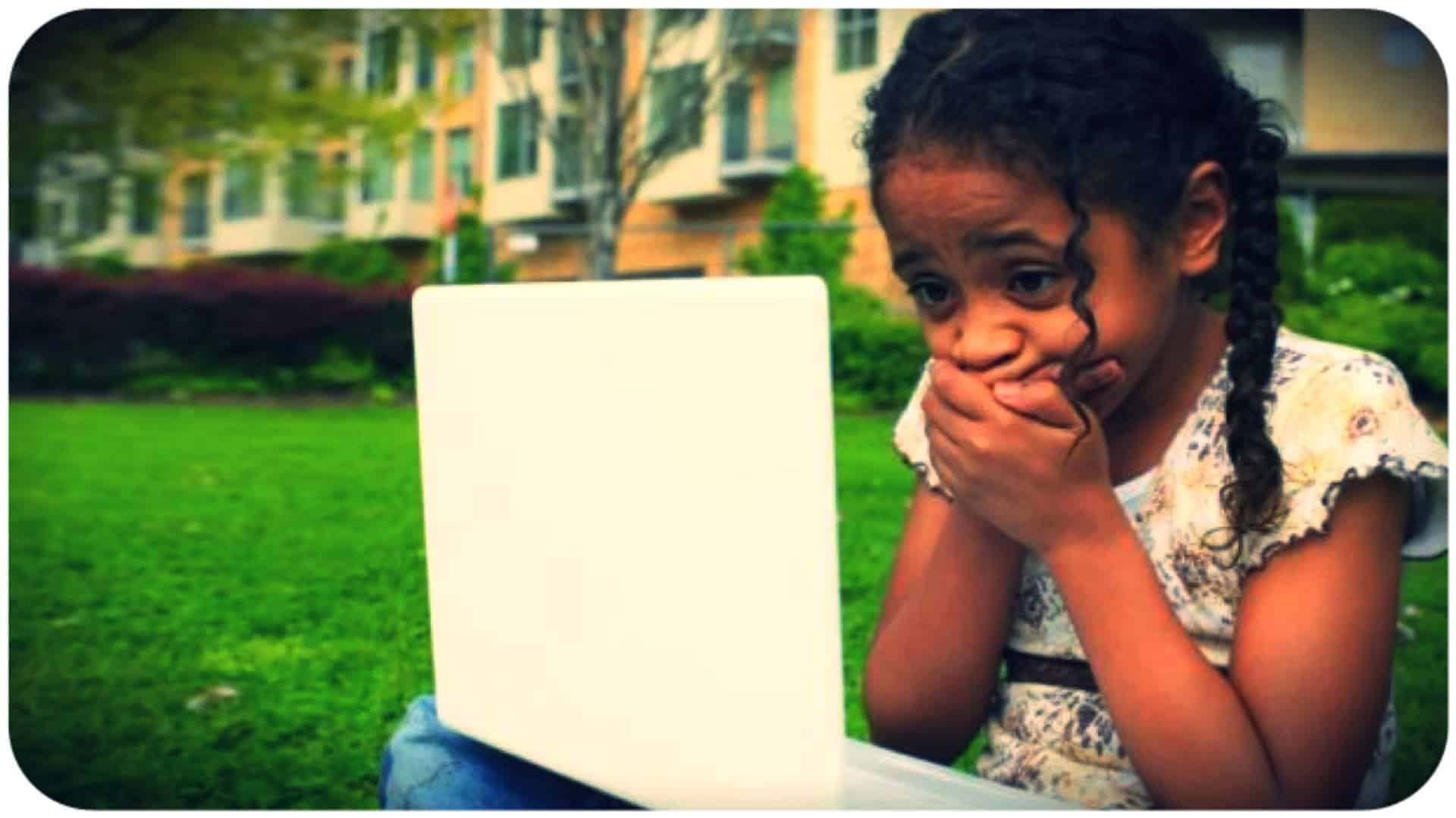 Young girl sitting on the grass in front of a row of buildings with a laptop open on her lap. she has her hands clasped over her mouth and she looks scared