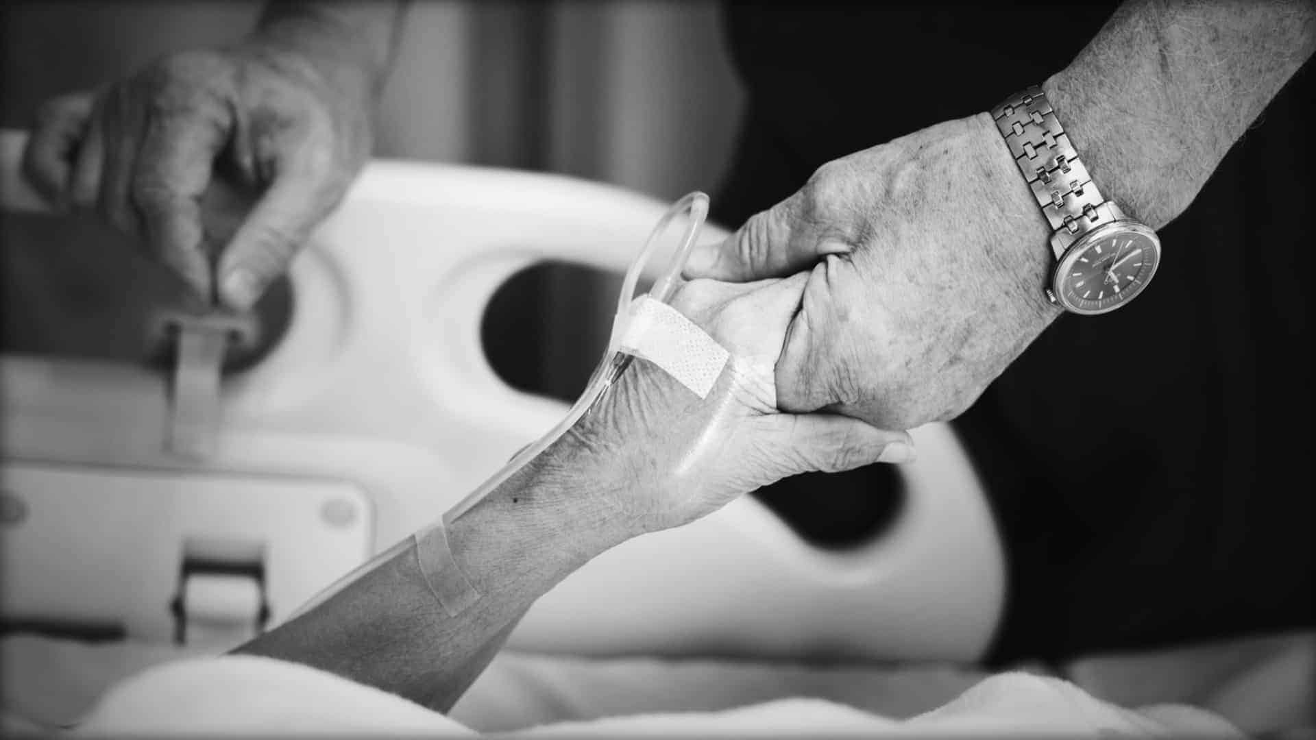 The image shows a close-up of hand. The hand is shown against the back drop of a hospital bed and has a drip needle inserted into the wrist. A caring hand and arm is seen holding the persons hand and giving comfort.