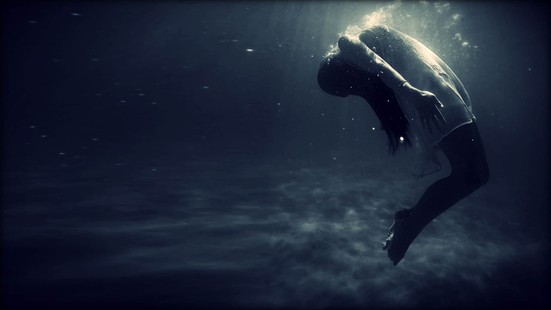 A fully dressed person is shown underwater. They are lit from above. The seabed is visible in the background. The person is arching backwards; their arms are at their sides and their legs bent at the knees. Air bubbles are escaping from their mouth.