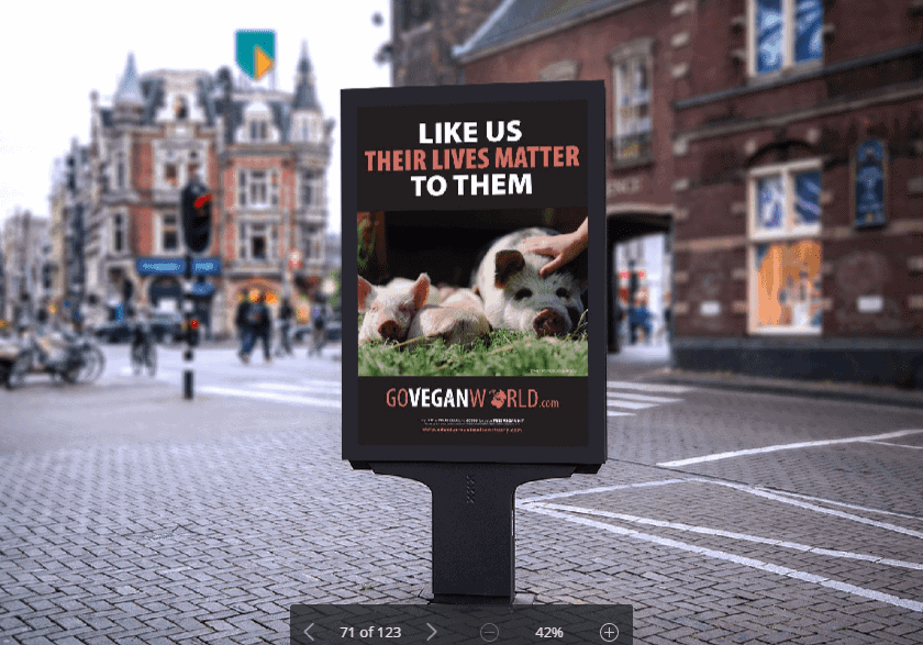 The image is of a high street, free standing double sided advertisement hording.  The hording depicts a poster from the GoVeganWorld.com campaign.  At the top are the words: Like us, their lives matter to them.  Below this is an image of a pig with two piglets.  A hand is shown stroking the head of the adult pig.  All three are led out in the sun on green field.  The campaign's logo is at the bottom of the poster.