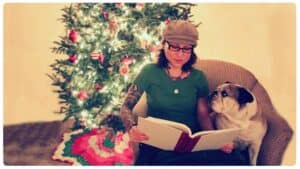 Emily Moran Barwick of Bite Size Vegan is shown sitting in a chair with her beloved bulldog, Ooby at her side and looking up at her. Emily is reading from a large book. Behind the tree is a fully decorated festive tree.