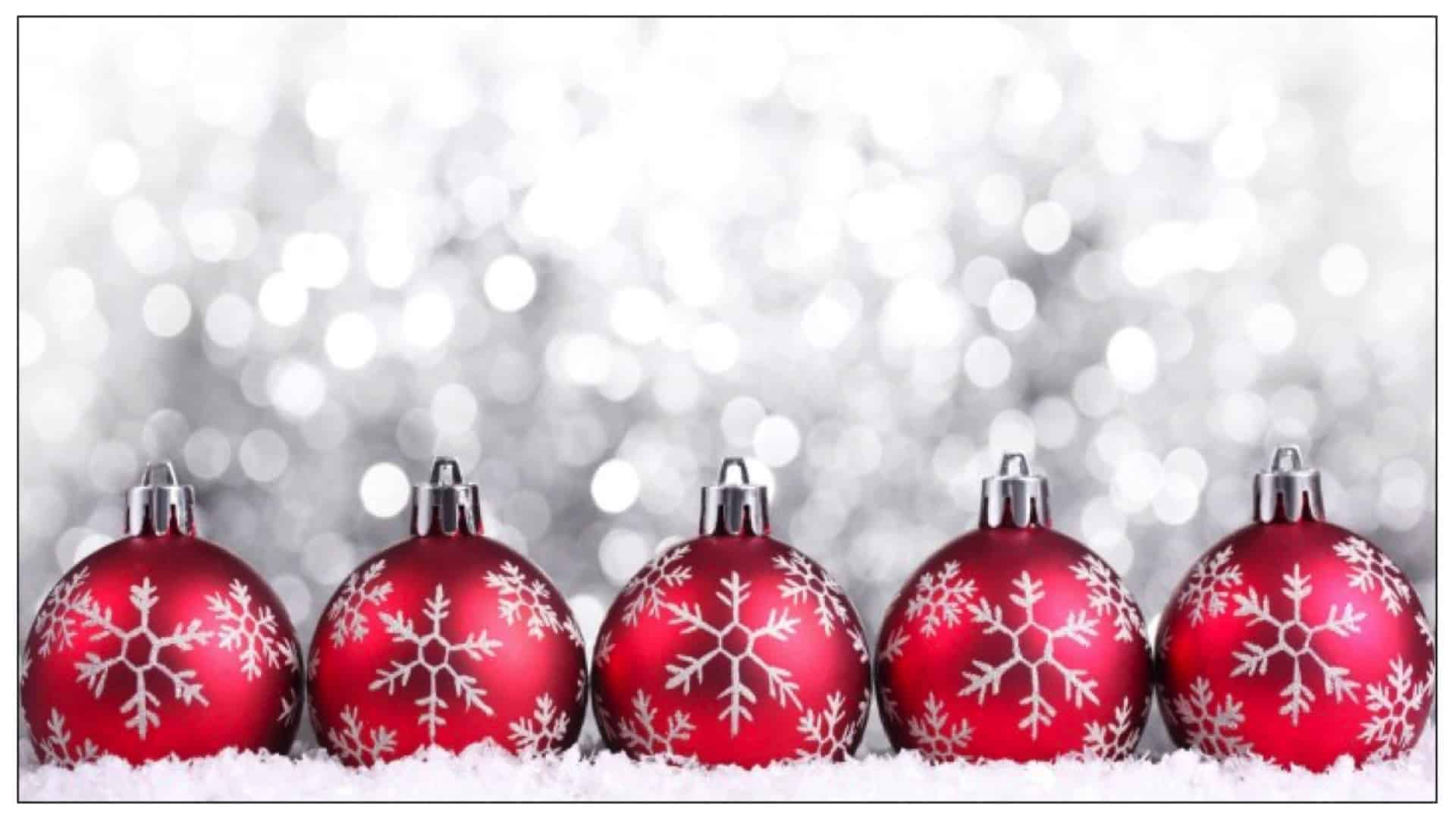 A row of red and silver festive baubles are shown across the bottom with a white, glittery background behind.