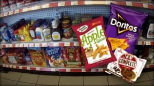 The image is of shelves of pre-packaged food, the sort you would expect to find in a grocery store or gas station. Overlaying the image is an image of some of the various vegan options typically available.