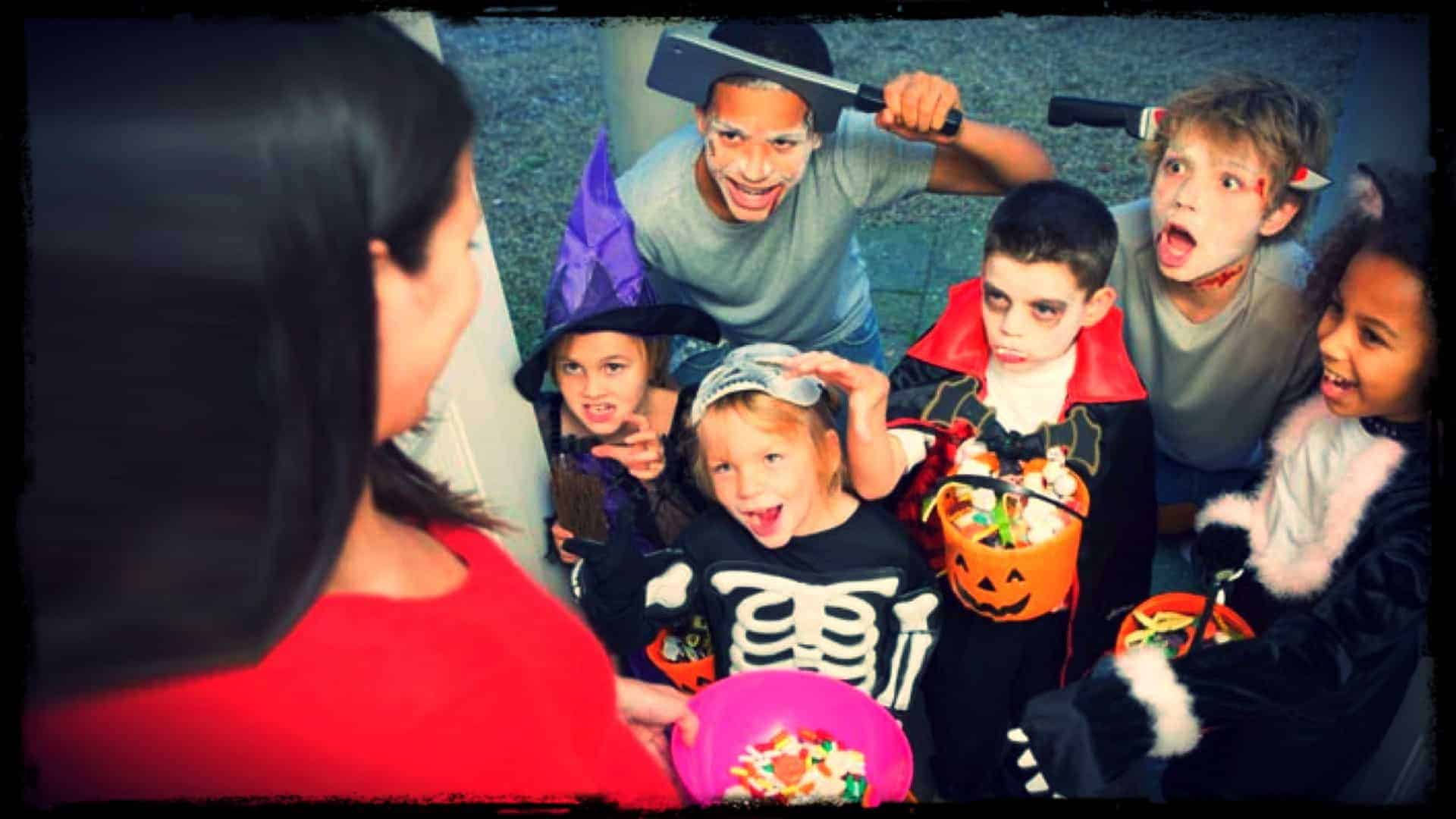 An adult is shown surrounded by children in Halloween costumes. The adult has a bowl of candy in their hand.