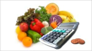 The image is made up of three elements. At the back is a glorious and colorful selection of fruit and vegetables. In front and to the side is a desk calculator. To the side of this are three coins.