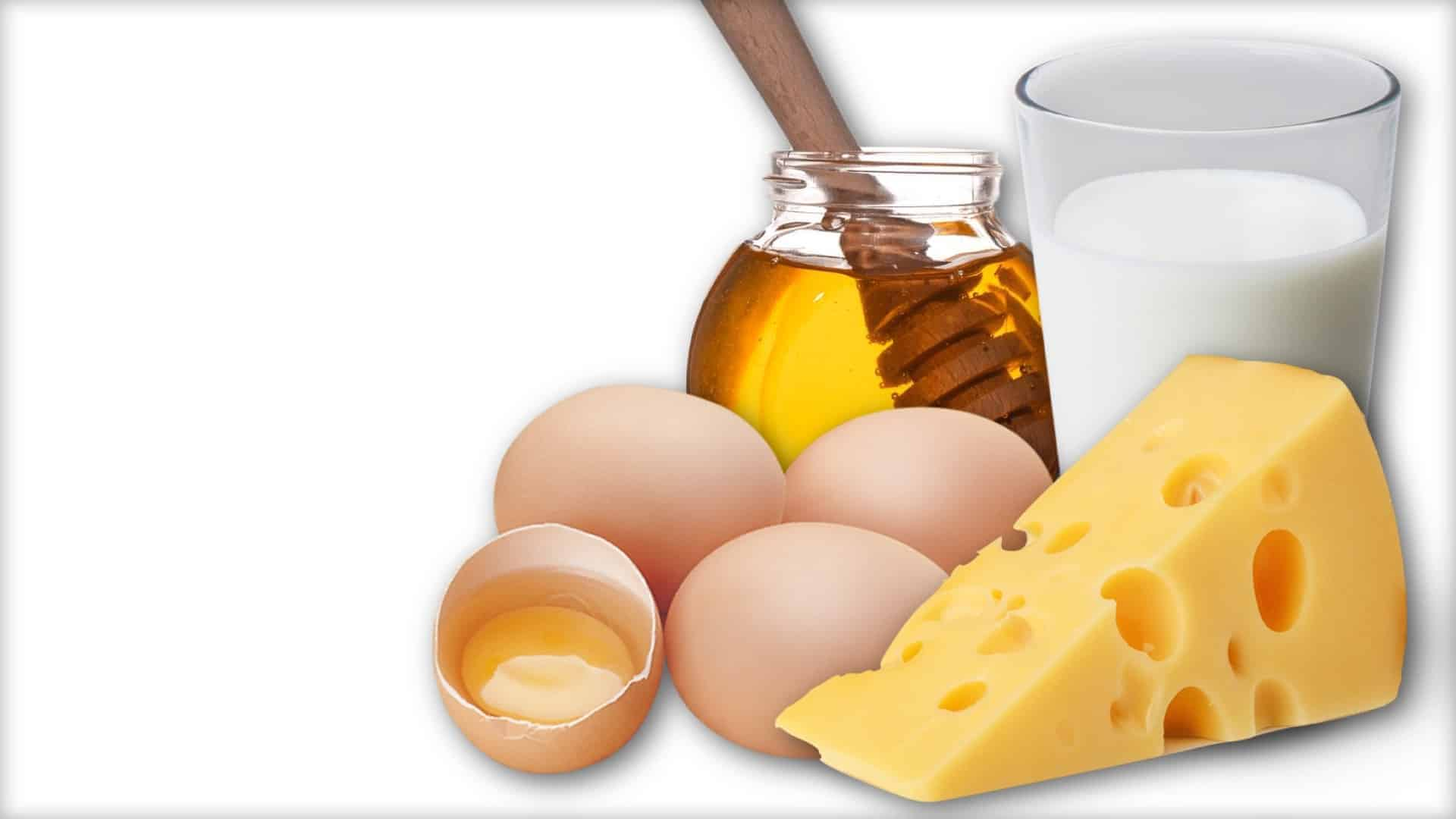 The image shows a number of hen's eggs, a chunk of cheese, a glass of honey and a jar of honey.