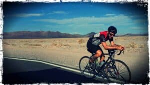 Vegan Ultra Athlete & Registered Dietitian, Matt Ruscigno, is shown on a racing bicycle and gear on the road. An open desert landscape is seen in the background.