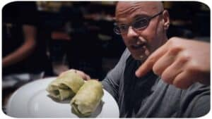Author and vegan activist Gary Yourofsky is shown pointing at a plate of delicious vegan food.