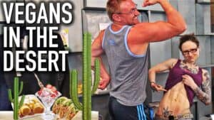 """Vegan bodybuilder Robert Cheeke is shown next to Emily Moran Barwick of Bite Size Vegan. Robert is flexing his arms in a bodybuilding pose. Emily has lifted up her shirt and is displaying her washboard abs. To the left of the pair is a table with a range of food on it. Shown above the food, in white letters are the words """"Vegans in the desert""""."""