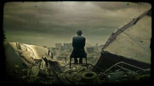 A seated figure, their back to the camera is shown under a dark and ominous sky. The figure looks toward a city skyline in the distance. They are surrounded by the rubble of a collapsed building and the discards of modern life.