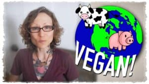 """Emily Moran Barwick of Bite Size Vegan is shown in close-up looking at the camera. To the right and overlaying the image is a cartoon earth with a cow and a pig """"floating"""" above it. Below the earth is the word """"Vegan!"""""""