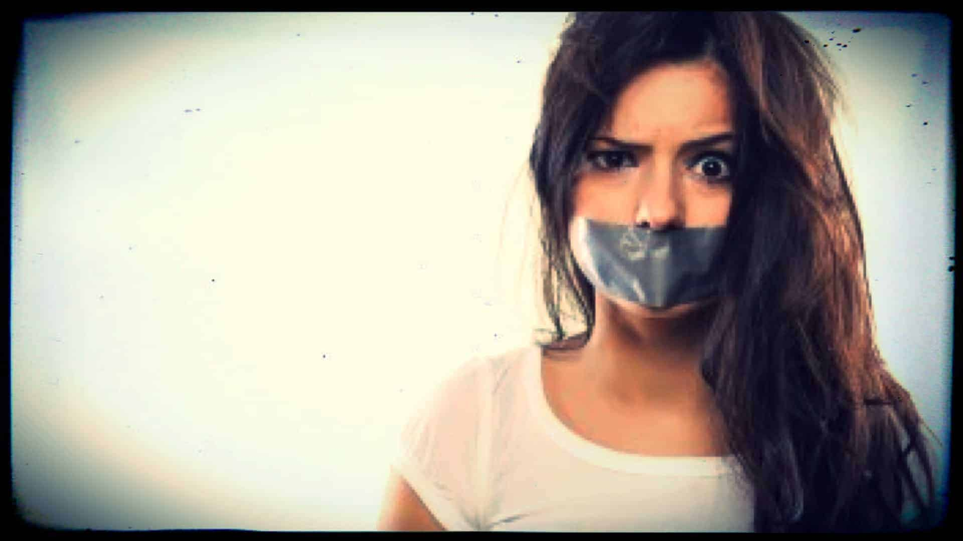 A person is shown from the shoulders up. They have grey tape across their mouth, silencing them. One eyebrow lifted in astonishment.